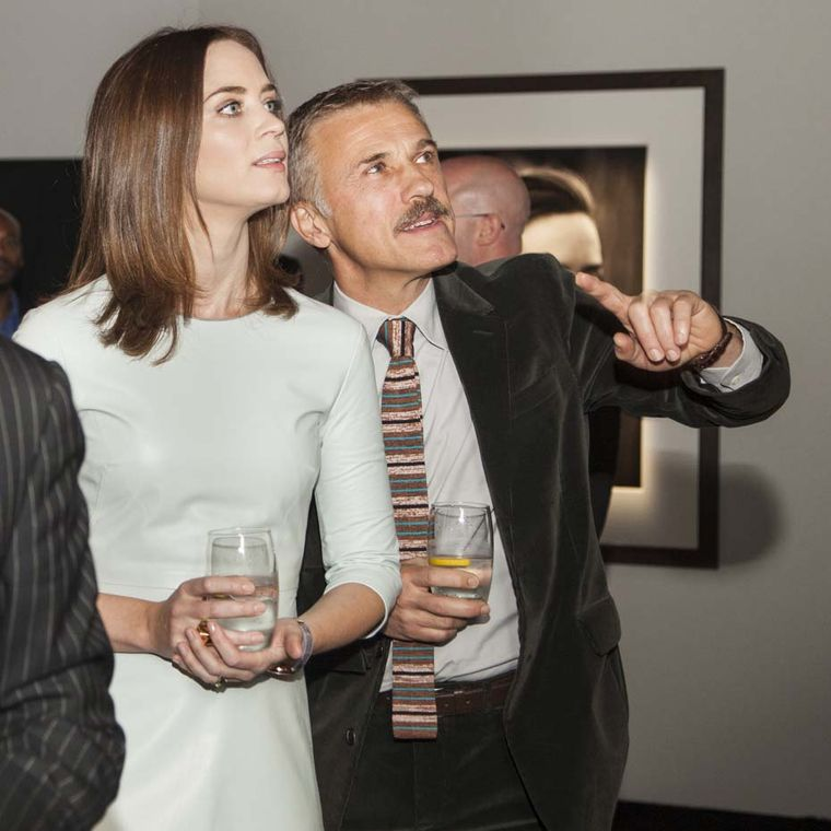 Emily Blunt and Christoph Waltz discuss one of Peter Lindbergh's photographs in the ''Timeless Portofino'' exhibition. Image by: PHOTOPRESS/IWC