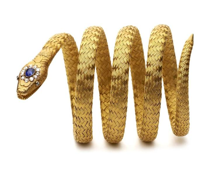 A Victorian sapphire and rose diamond gold coiled bracelet ending in a snake's head with an open mouth and two rose-cut diamond eyes and a rose-cut diamond and pear-shaped sapphire head. Exhibited by Hancocks.