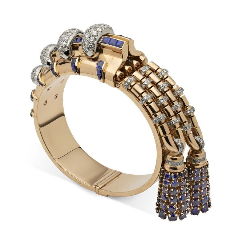 Rose gold bangle set with calibre-cut sapphires, with links decorated in brilliant-cut diamonds set in platinum and hung with two tassels set with brilliant-cut sapphires by Boucheron, Paris 1944/46. Exhibited by Hancocks.