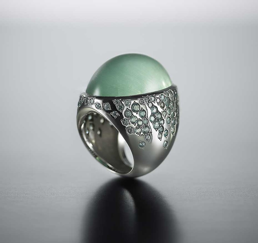 Walid Akkad cabochon green beryl ring with streams of green-grey sapphires and diamonds set on the shoulders.