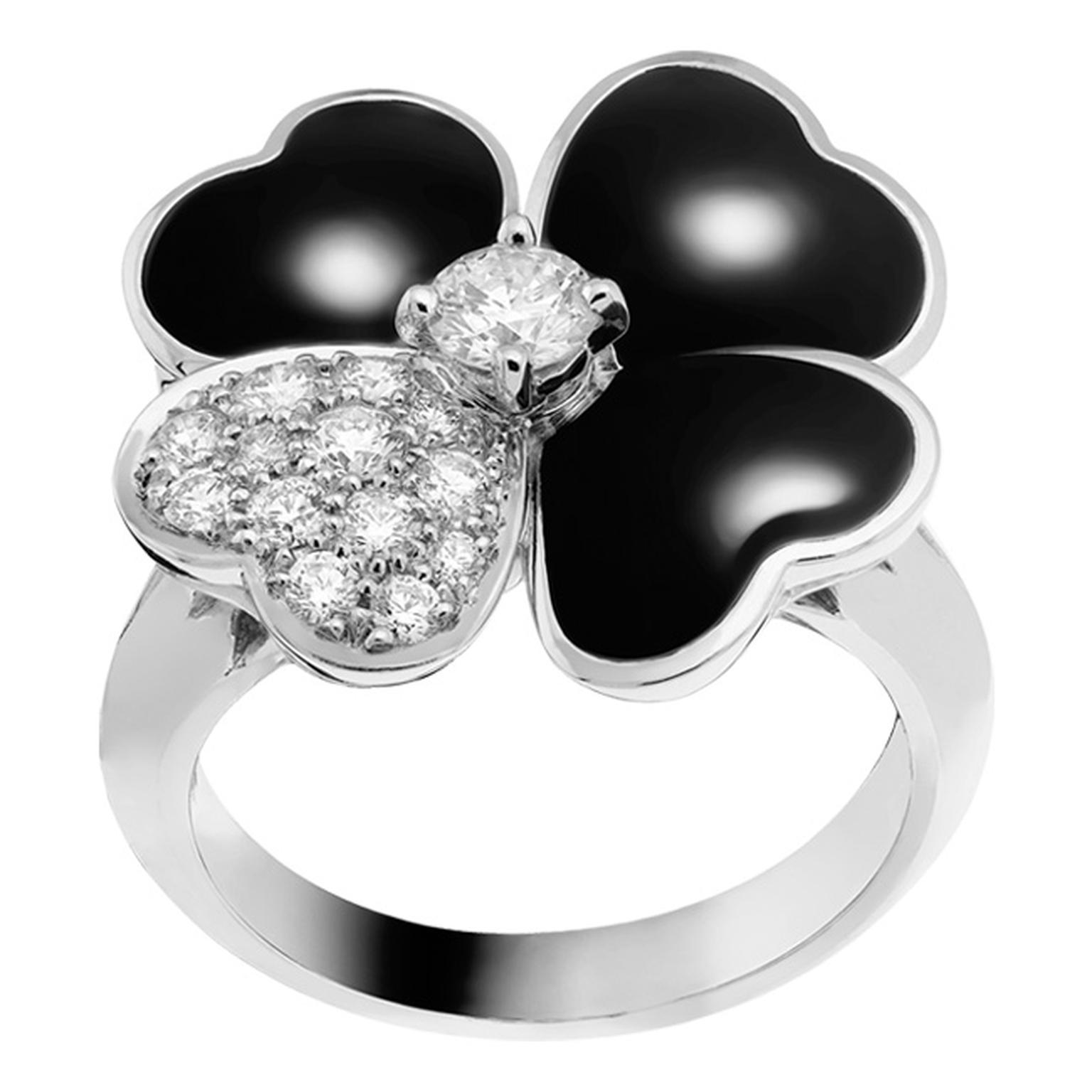 Van Cleef & Arpels Cosmos ring in white gold with a brilliant-cut diamond bud surrounded by onyx and diamond petals.