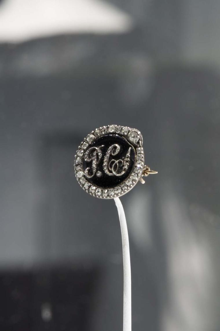 A gold Mourning brooch with the loved one's initials inscribed in diamonds set in onyx and surrounded by diamonds.