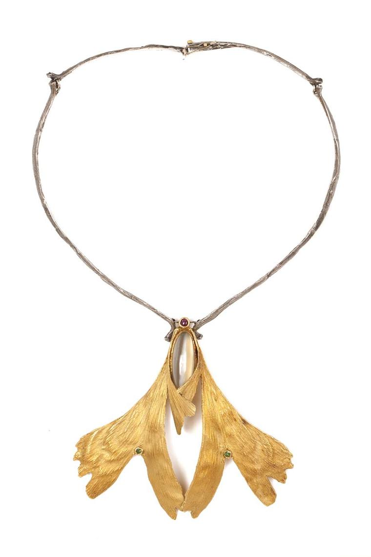Elizabeth Defner necklace featuring two gold chased ginko biloba leaves set with round mixed-cut emeralds, supporting a honey coloured moonstone and a round mixed-cut ruby