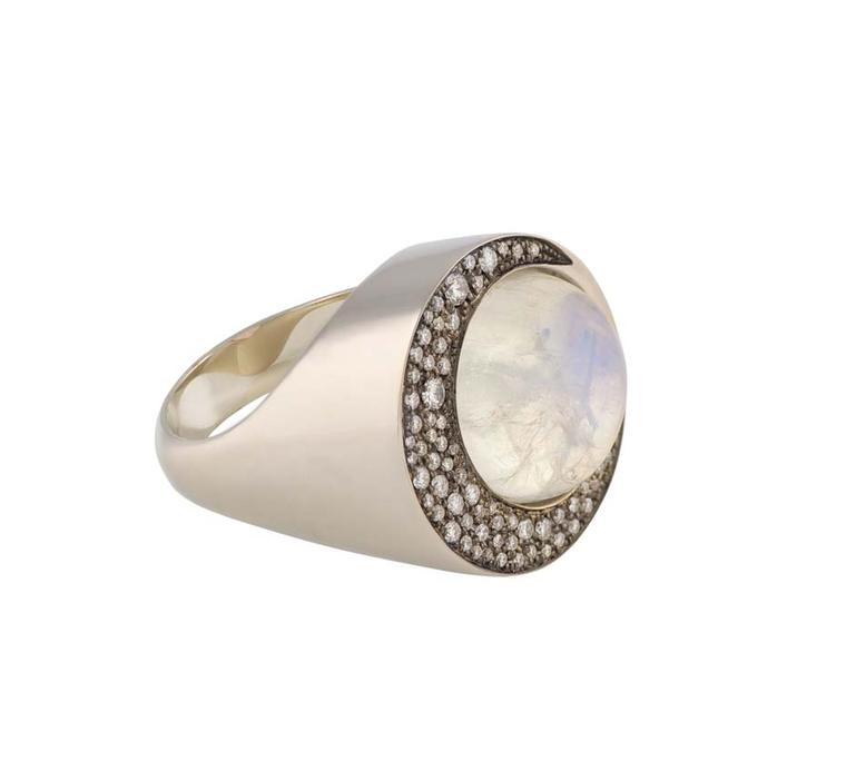 Noor Fares Eclipse ring with a blue moonstone centre set in grey gold surrounded by a crescent of white diamonds in black rhodium.