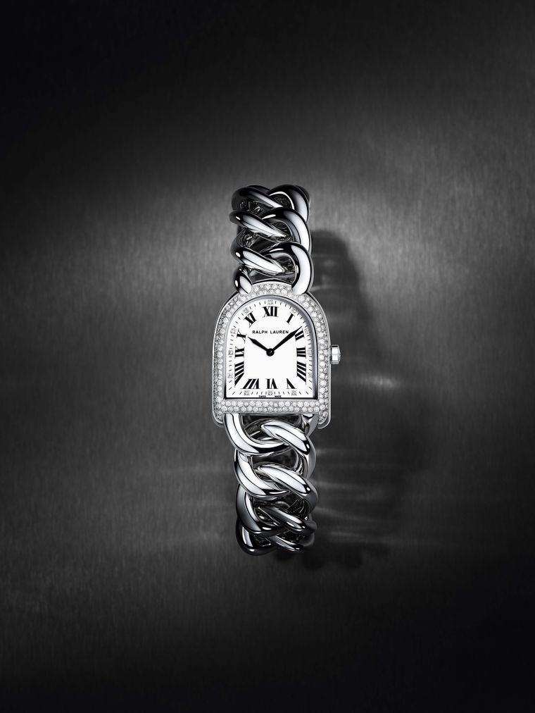 Ralph Lauren's Petite-Link Stirrup watch is covered with a white mantle of 148 diamonds on the bezel and case using the snowfall diamond-setting technique. The sparkling diamonds of different sizes appear to have settled on the case like ethereal snowflak