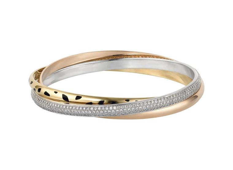 The Cartier Trinity Sauvage bracelet is a cool interpretation of the classic Trinity collection, with a white gold band pavéd with diamonds, a yellow gold band with black lacquer spots and a pink gold band engraved with Cartier.
