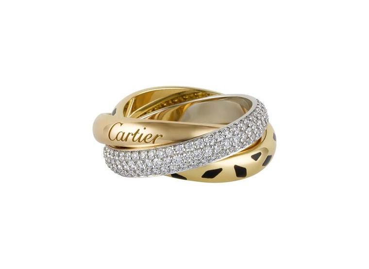 Cartier Trinity Sauvage ring featuring a white gold band pavéd with diamonds, a yellow gold band with black lacquer spots and a pink gold band engraved with Cartier.