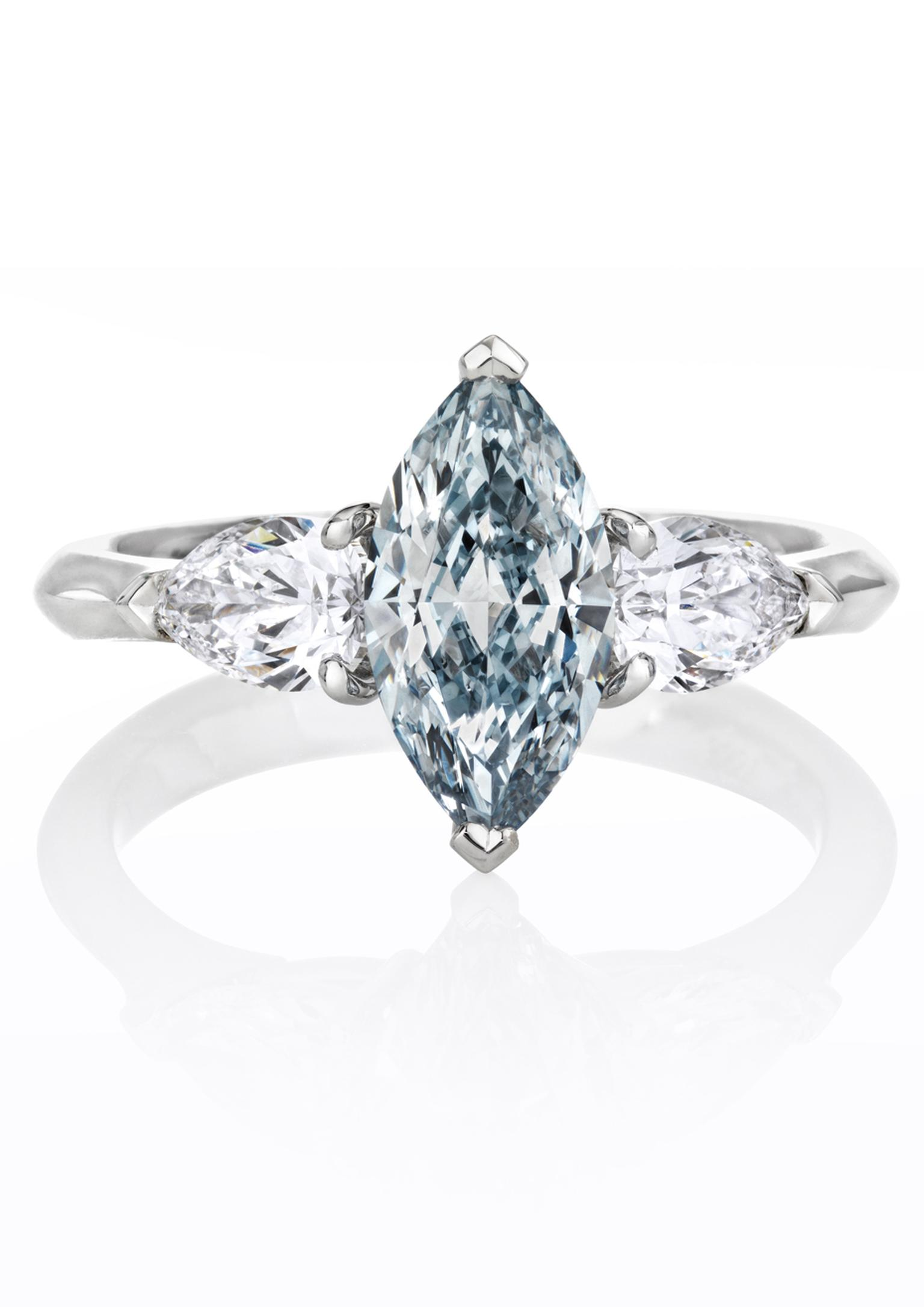 De Beers marquise-shaped blue diamond engagement ring flanked by white diamonds.