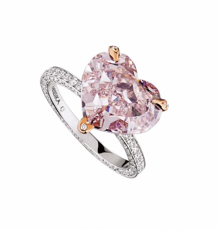 Messika heart-shaped pink diamond engagement ring set with rose gold prongs and a pavé diamond band.