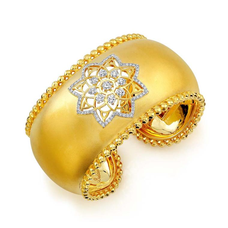 Buddha Mama Dharma Wheel cuff with a cut-out diamond mandala and hollow spheres around the borders ($28,400).