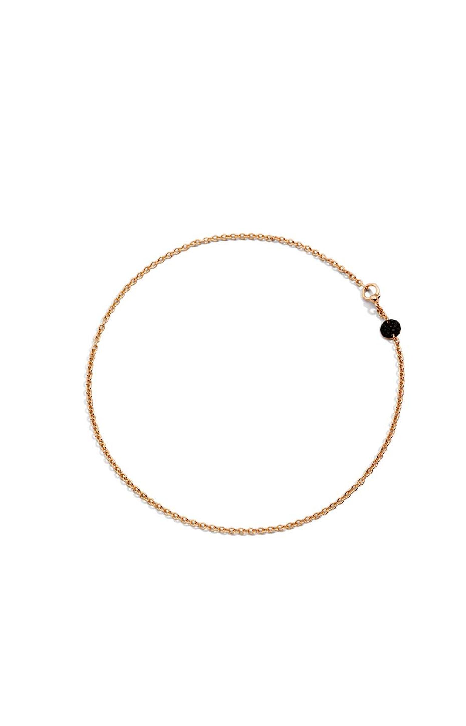 Pomellato Sabbia choker necklace featuring a rose gold disc with black diamonds.
