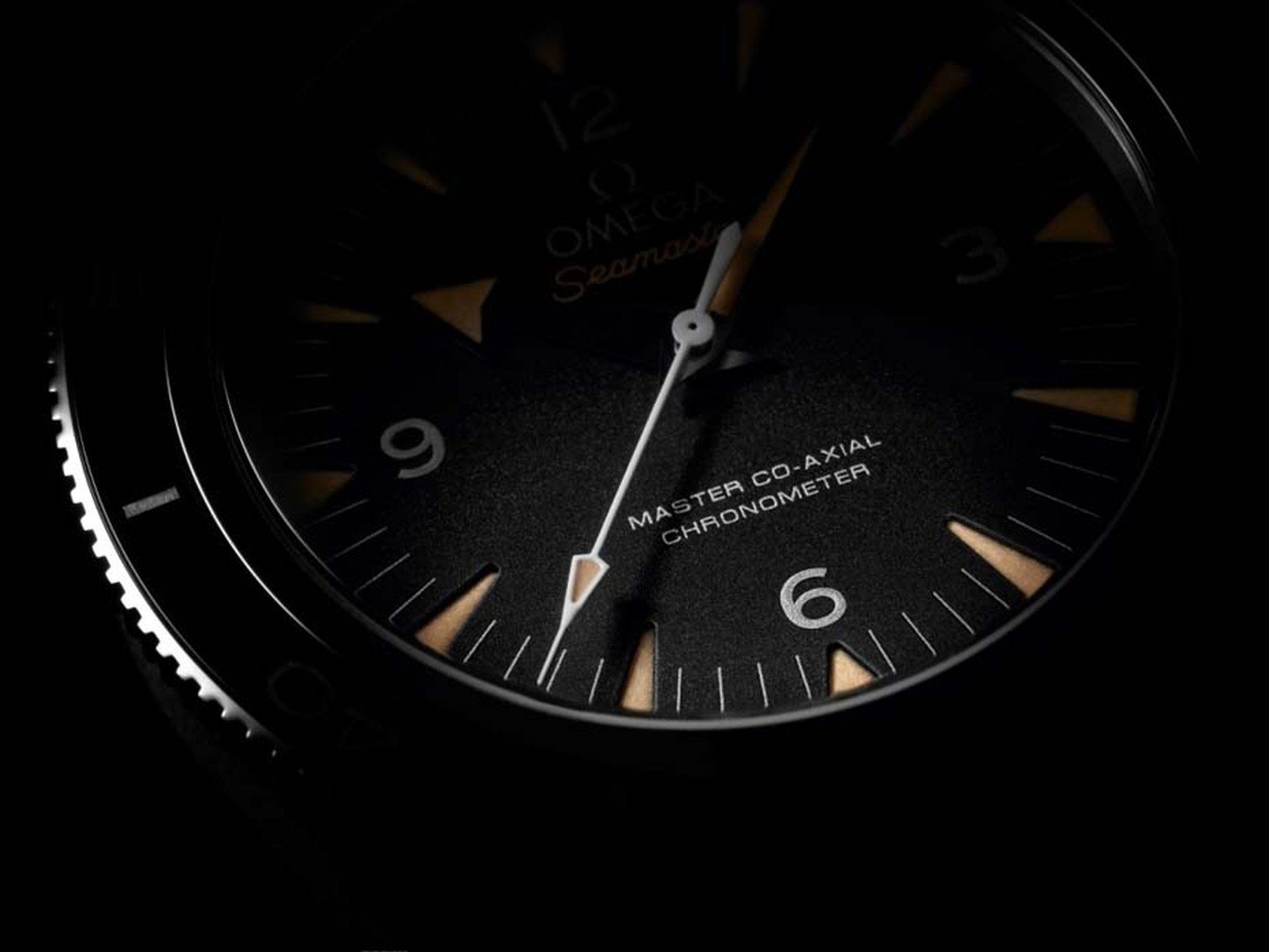 The Omega Seamaster 300 Master Co-Axial 41mm watch features a black sandblasted dial which offsets the beige vintage SuperLumiNova hour markers.