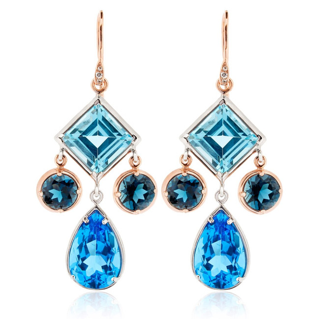 Dinny Hall Amelie Anniversary earrings featuring Ostro, London and Swiss blue topaz with sterling silver and rose gold. The mini chandelier earrings, with the three blue hues and three different gemstone cuts, showcase Dinny Hall's signature bohemian styl