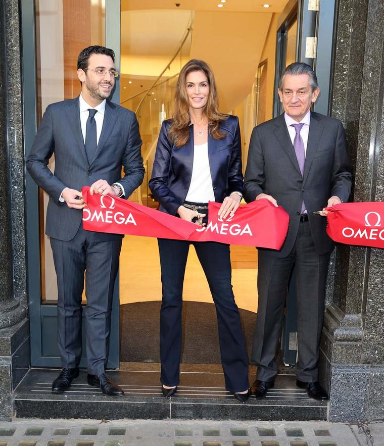Omega ambassador Cindy Crawford cuts the traditional red ribbon alongside Omega President Stephen Urquhart, right, to officially open the brand's flagship boutique on London's Oxford Street.