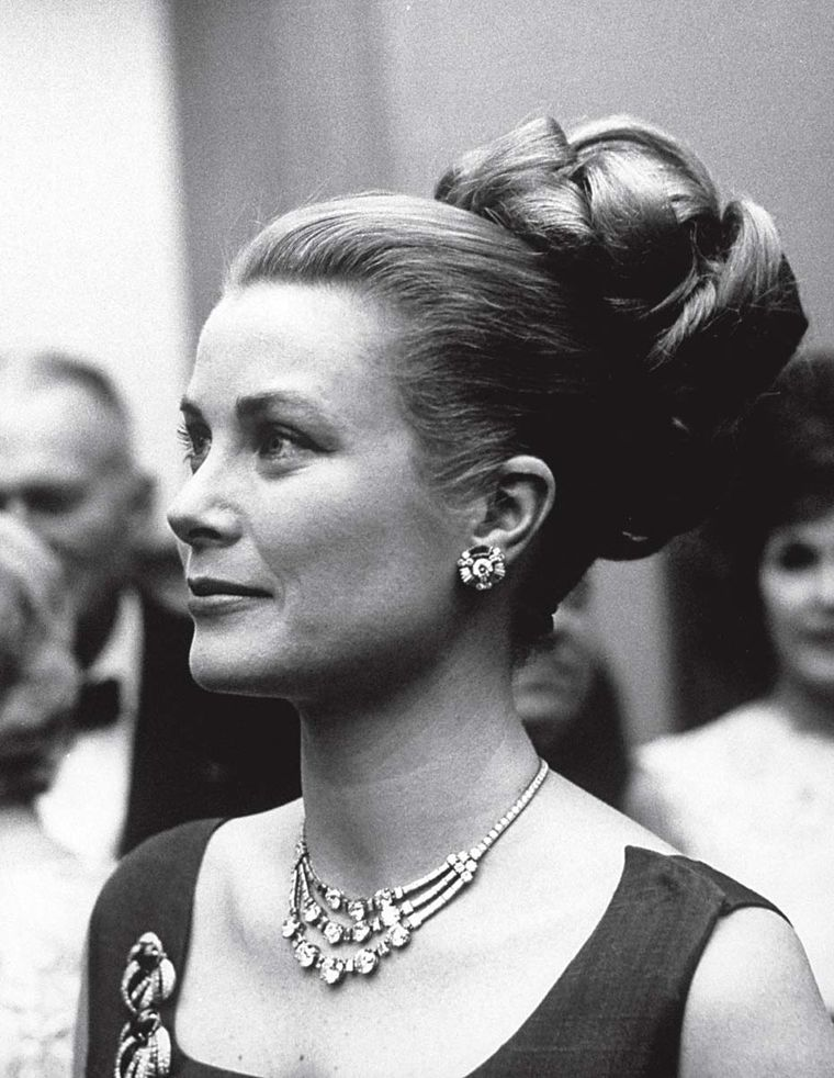 Princess Grace of Monaco at a reception in Philadelphia wearing a Cartier necklace in platinum and diamonds that she received as a wedding gift in 1956. The necklace was recreated by Cartier for the 2014 film Grace of Monaco starring Nicole Kidman. (Photo