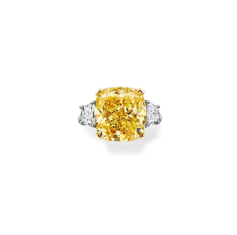 Harry Winston Classic Winston emerald-cut yellow diamond engagement ring in platinum with two brilliant-shaped diamond side stones.