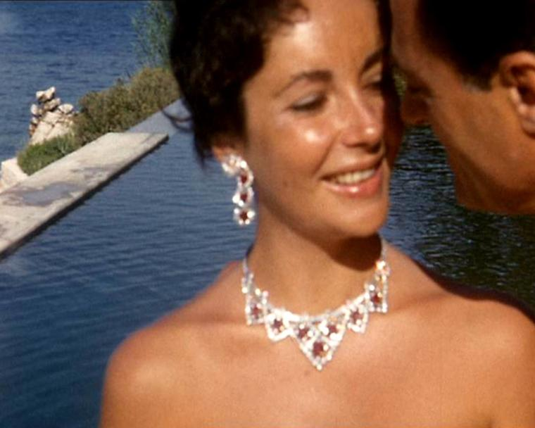 Elizabeth Taylor in 1957 wearing the Cartier ruby jewellery set just given to her by Mike Todd - she later jumped into the pool, rubies and all. © Premium Archive Films/Getty Images