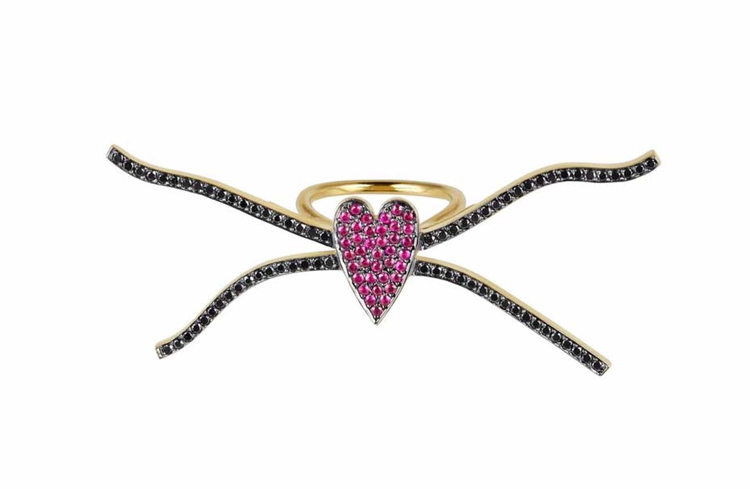 Elena Votsi Eros across-the-finger ring in yellow gold with rubies and black diamonds.