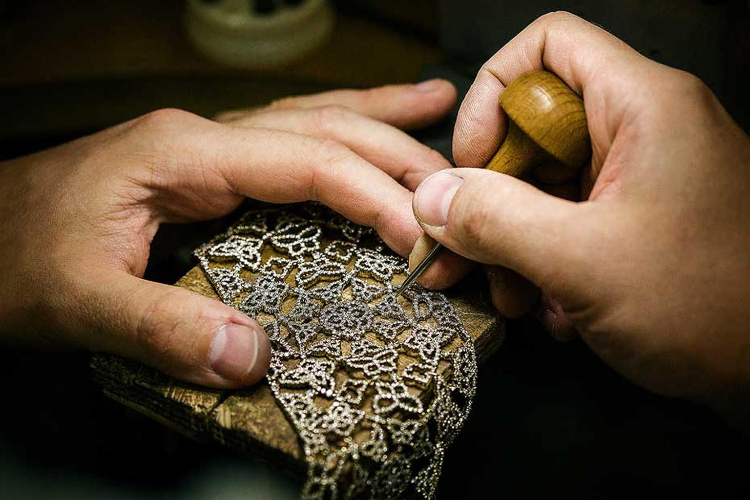 A craftsman sets diamonds into an intricate jewel in Alexander Arne's workshop.