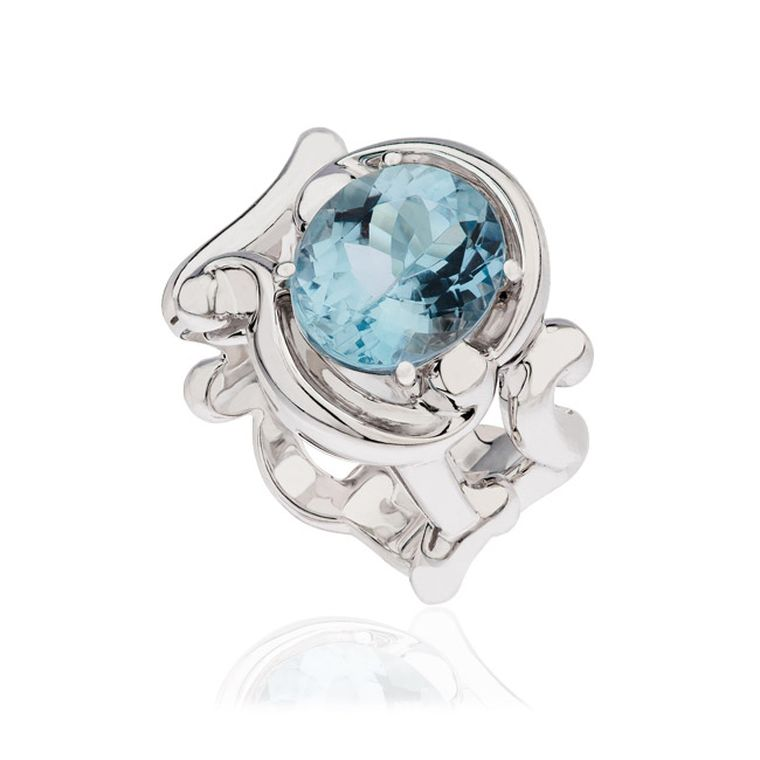 The lavish aquamarine and white gold cocktail ring from the Rococo collection by Fabergé features a sky blue, faceted, oval-cut aquamarine.