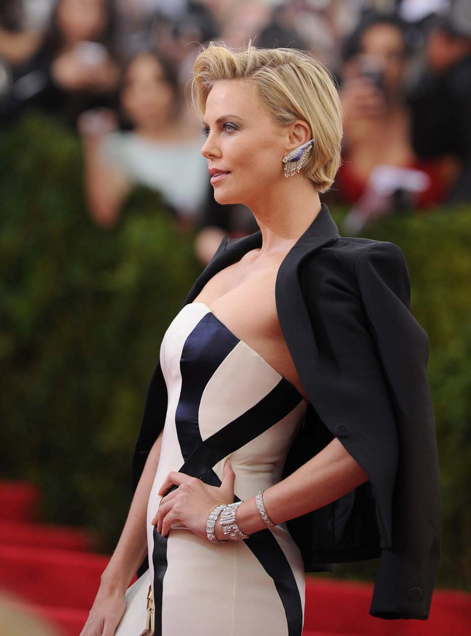 Actress Charlize Theron walks the 2014 Met Gala red carpet wearing vintage-inspired Fred Leighton diamond wing earrings with ombre enamelled feathers.