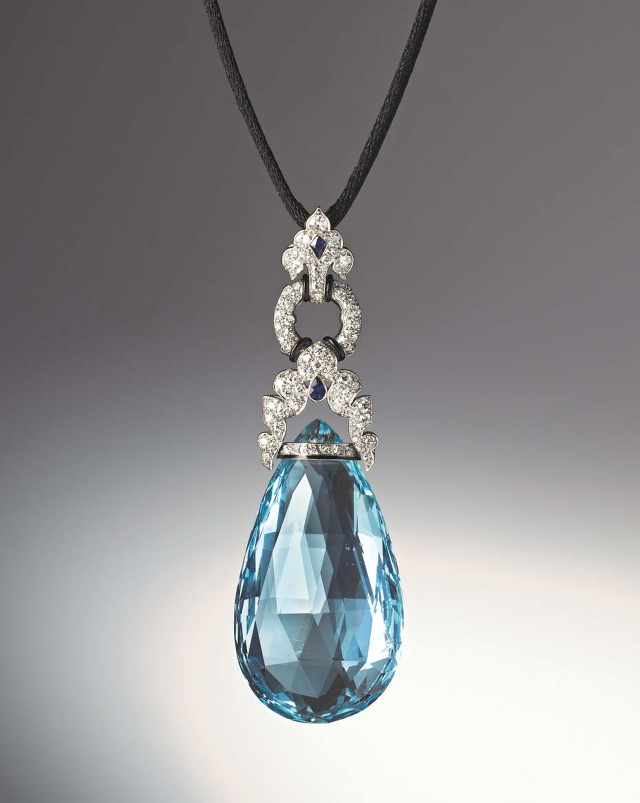 Art Deco aquamarine briolette pendant set with diamonds, two fancy-cut sapphires, as well as bands of black enamel set in platinum by Marzo, Paris, circa 1925. Available at Hancocks.