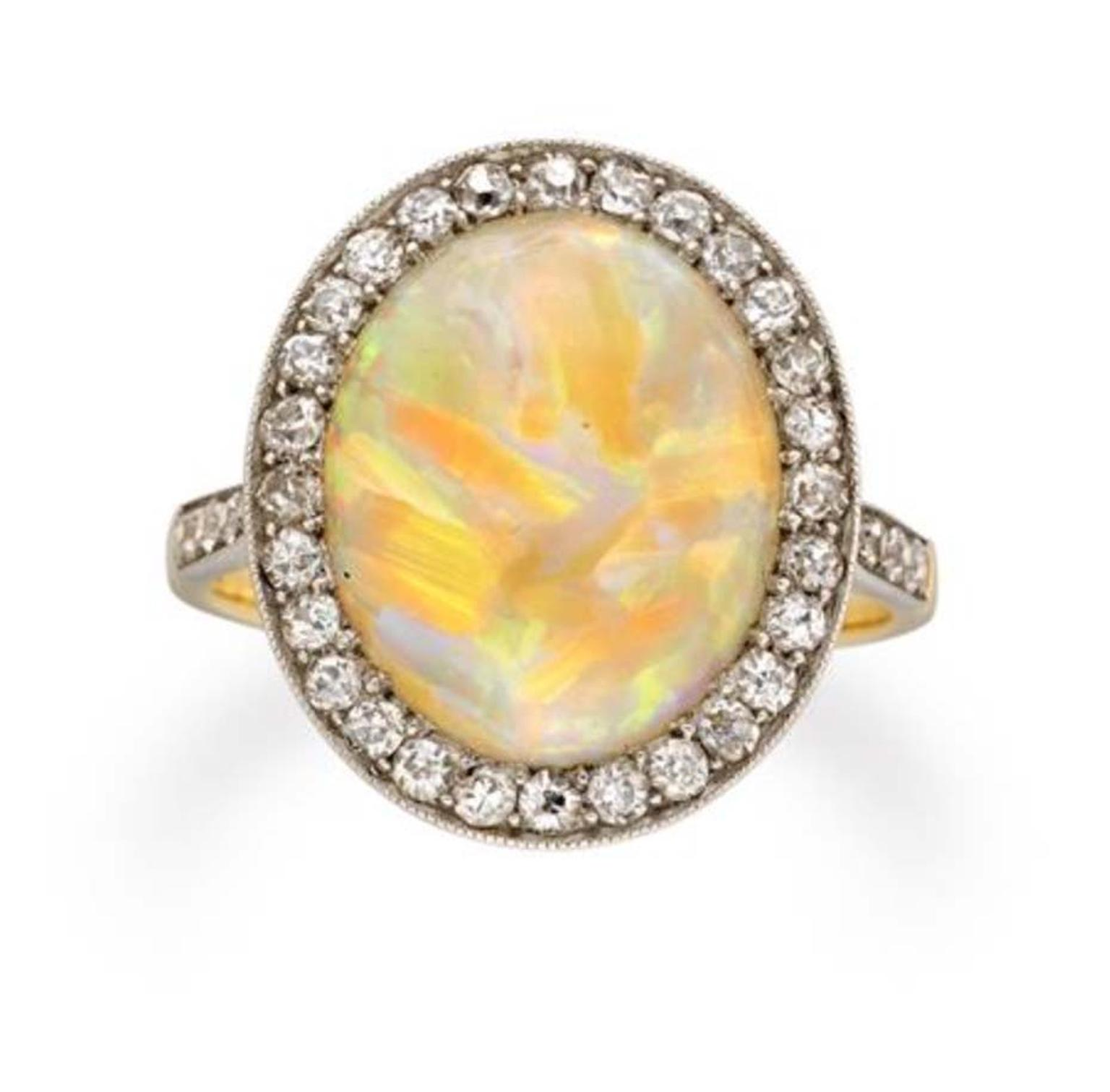 This Edwardian opal and diamond cluster ring circa 1910, available at Bentley & Skinner, has an oval cabochon opal set in the centre of an eight-cut, diamond-set surround, millegrain-set, with diamond-set shoulders.