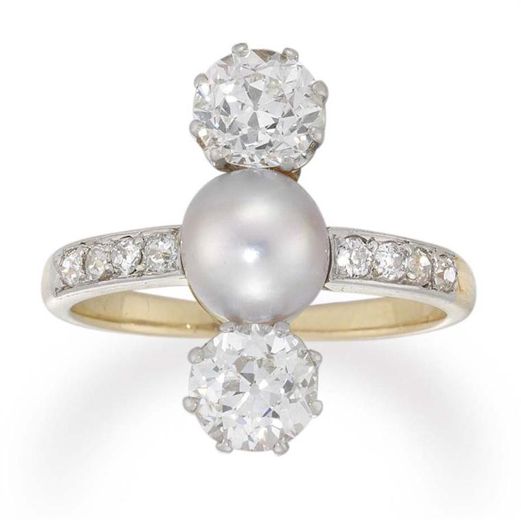 This beautiful Edwardian diamond and cultured pearl three-stone ring circa 1910, available at Bentley & Skinner, has a central cultured pearl set between two old brilliant-cut diamonds, all vertically set, to a gold open-backed mount with diamond-set shou