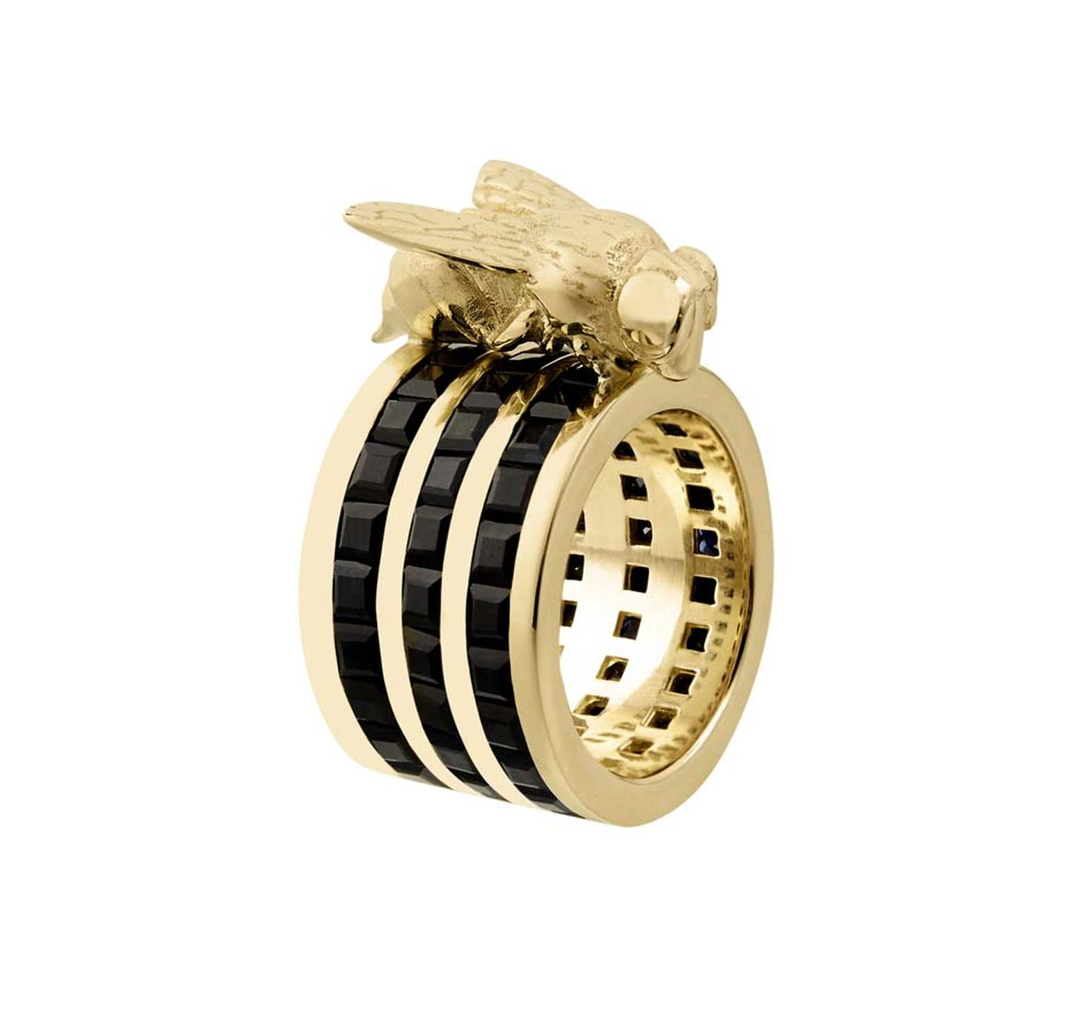 Tessa Packard's 18ct yellow gold Cocktail Sting ring from the Predator/Prey collection, featuring three bands of channel-set black sapphires topped with a solid gold wasp.