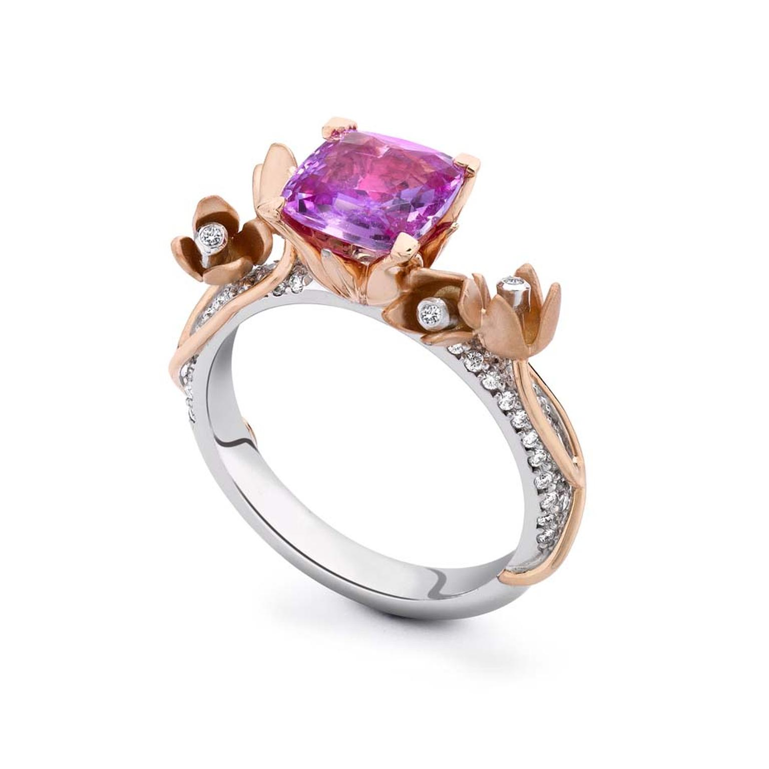 Theo Fennell engagement ring featuring a cushion-cut pink sapphire nestled in a rose gold floral setting on a white gold pavé band.