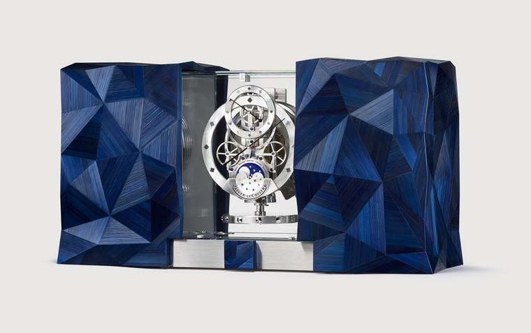 Jaeger-LeCoultre celebrates the cosmos with the Atmos Marqueterie Paille table clock. The  wooden cabinets at either side of the clock feature pyramid-shaped structures made from blue-tinted straw marquetry. By sliding open the doors, the Atmos clock, whi