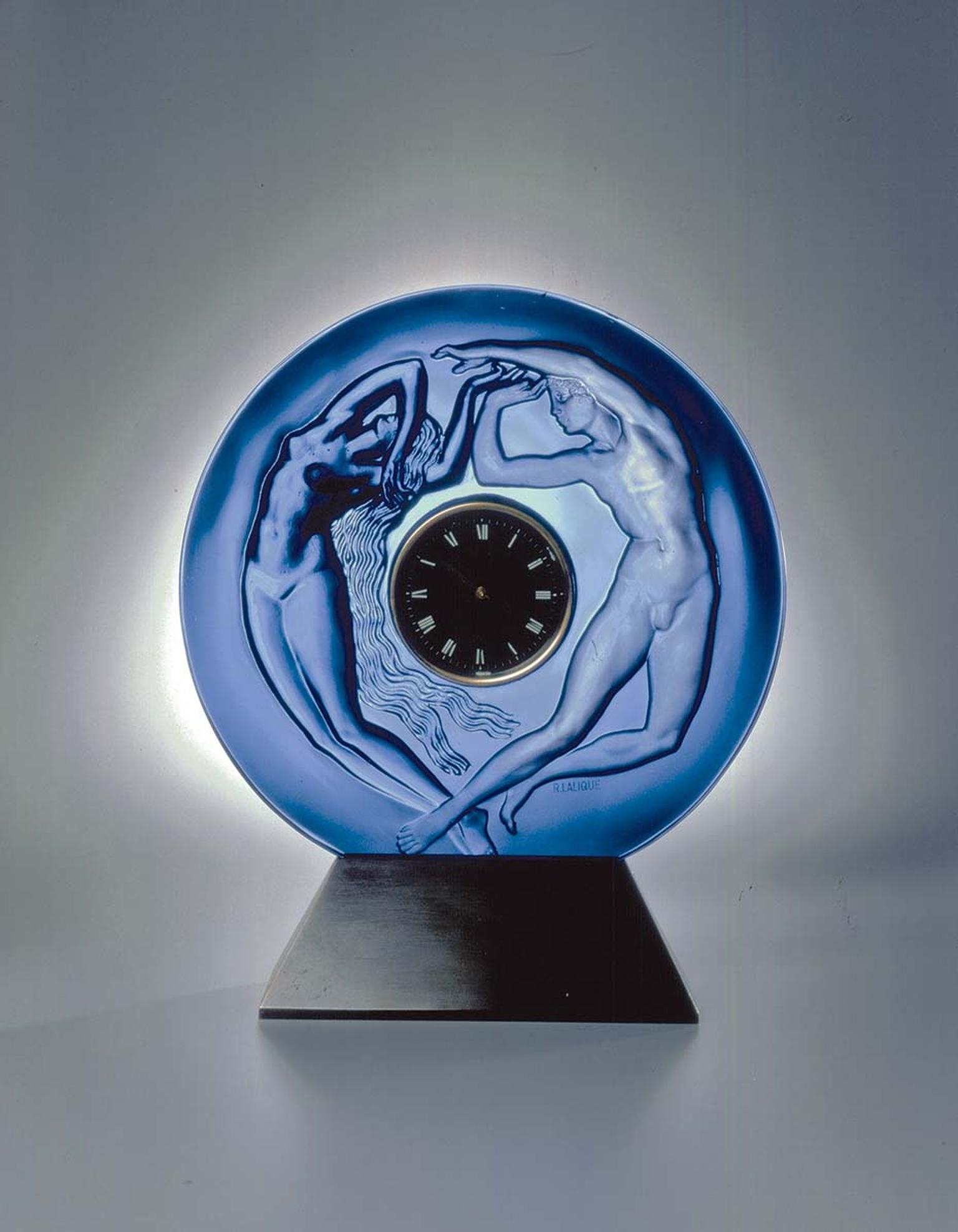 René Lalique's original Le Jour et la Nuit table clock of 1926 depicts a woman in relief on polished glass (night) and a man in counter-relief on satin-finished glass (day). The same mould has been used to create this new table clock, a collaboration betw