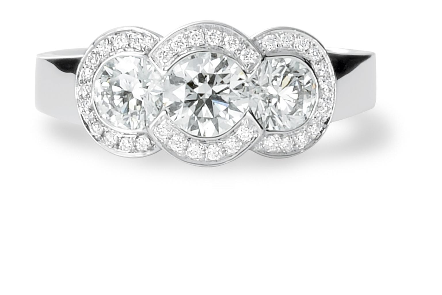 David M Robinson three stone engagement ring with diamond surround.