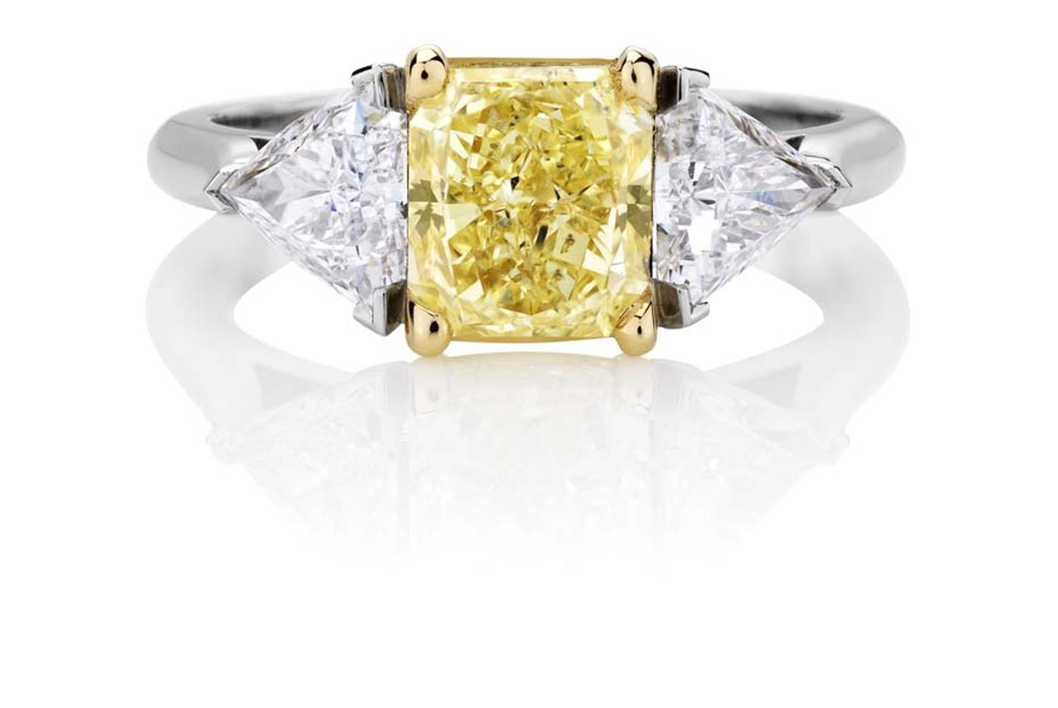 Part of De Beers jewellery's 1888 Master Diamonds collection, a three stone engagement ring set with a 3.93ct vivid yellow diamond flanked by trilliant-cut diamonds.