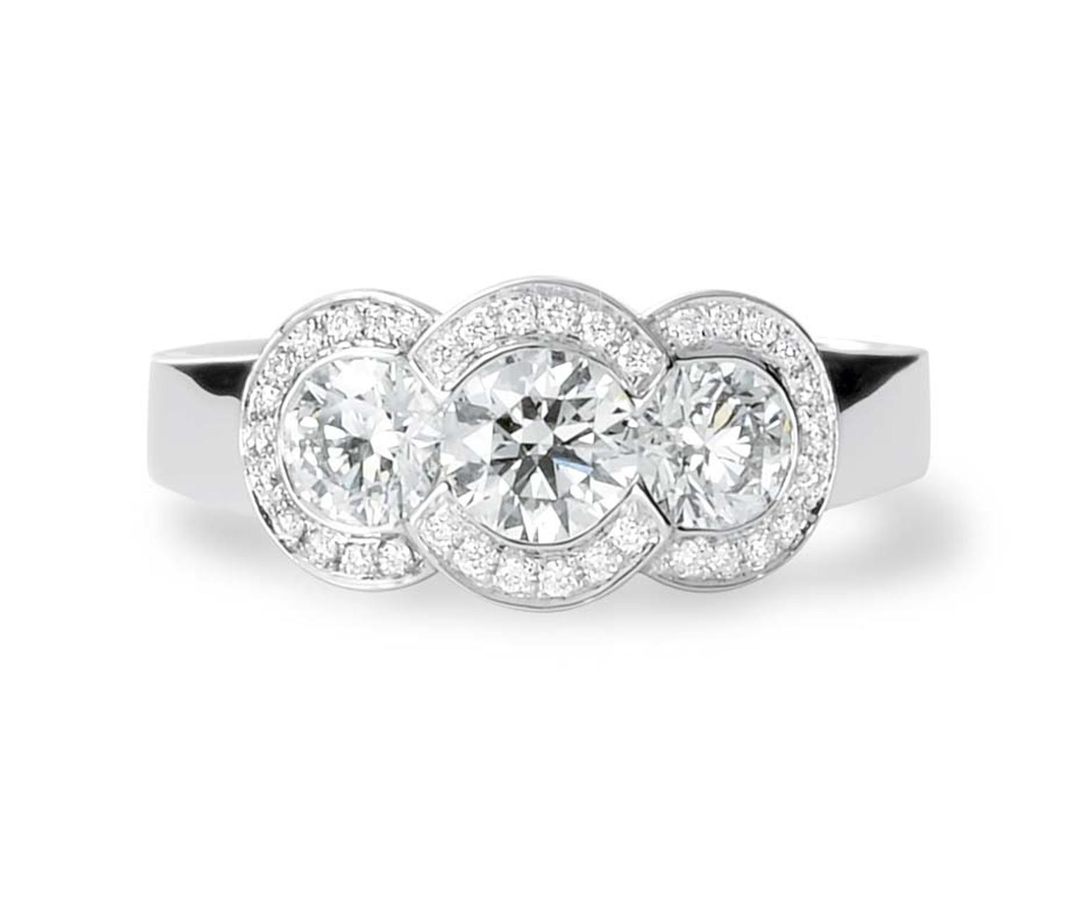 David Robinson's three stone engagement ring is set with three solitaires diamonds in a halo-style surround.