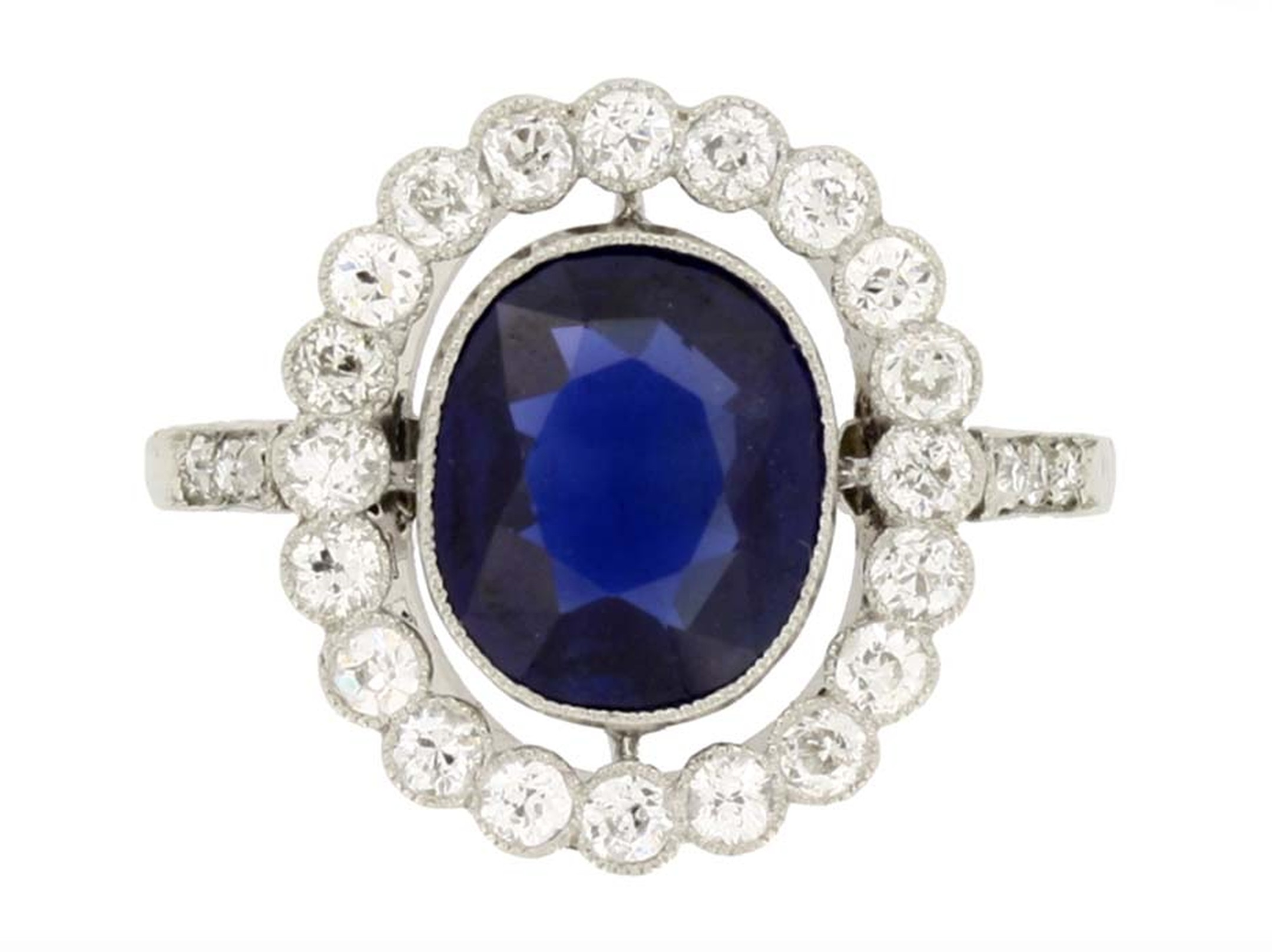 This Edwardian marquise sapphire and diamond cluster engagement ring circa 1910, available at Berganza, is set with a marquise shape, old-cut, natural unenhanced sapphire, encircled by a single row of round, old, single-cut diamonds of varying sizes, with