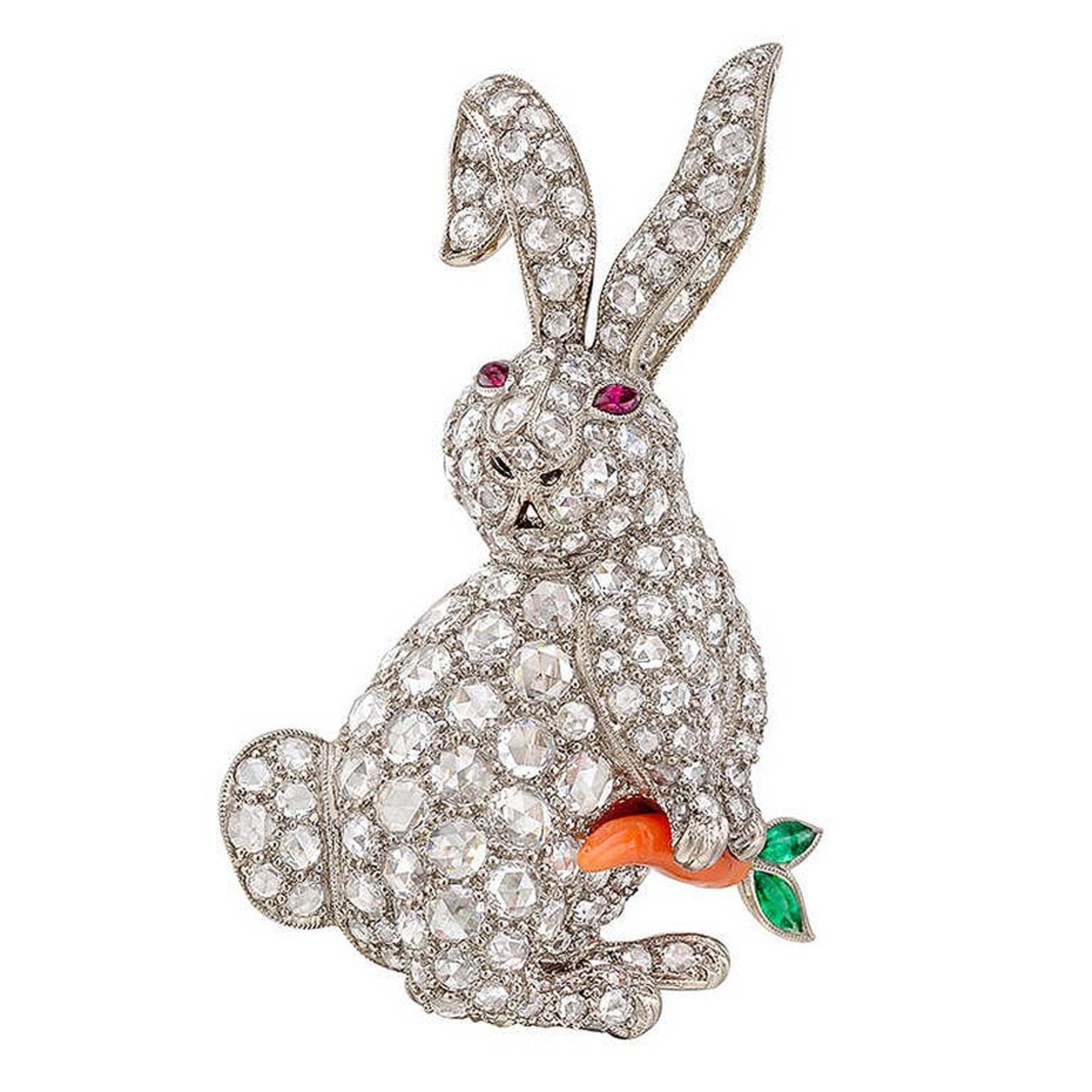 1stdibs white gold rabbit antique jewellery brooch featuring circular-cut diamonds, ruby eyes, and a carved coral carrot with emerald leaves, dates back to the 20th century.