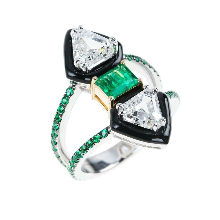 "Nikos Koulis creates a powerful silhouette for his new ""Oui"" collection of unique engagement rings using black enamel. This diamond engagement ring is set with a central emerald and additional pavé emeralds around the double band."