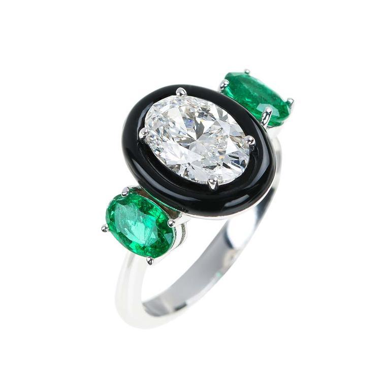 "This unique engagement ring from the new ""Oui"" bridal collection from Nikos Koulis features an oval-cut diamond encased in black enamel with two emeralds either side."