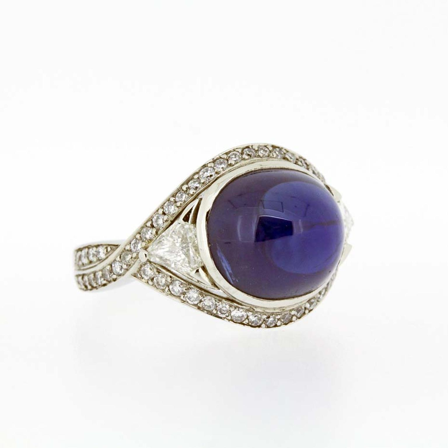 A unique sapphire engagement ring from Brighton-based Baroque Jewellery in white gold set with a large blue cabochon sapphire, flanked by trillion-cut diamonds with grain-set diamonds on the shank.