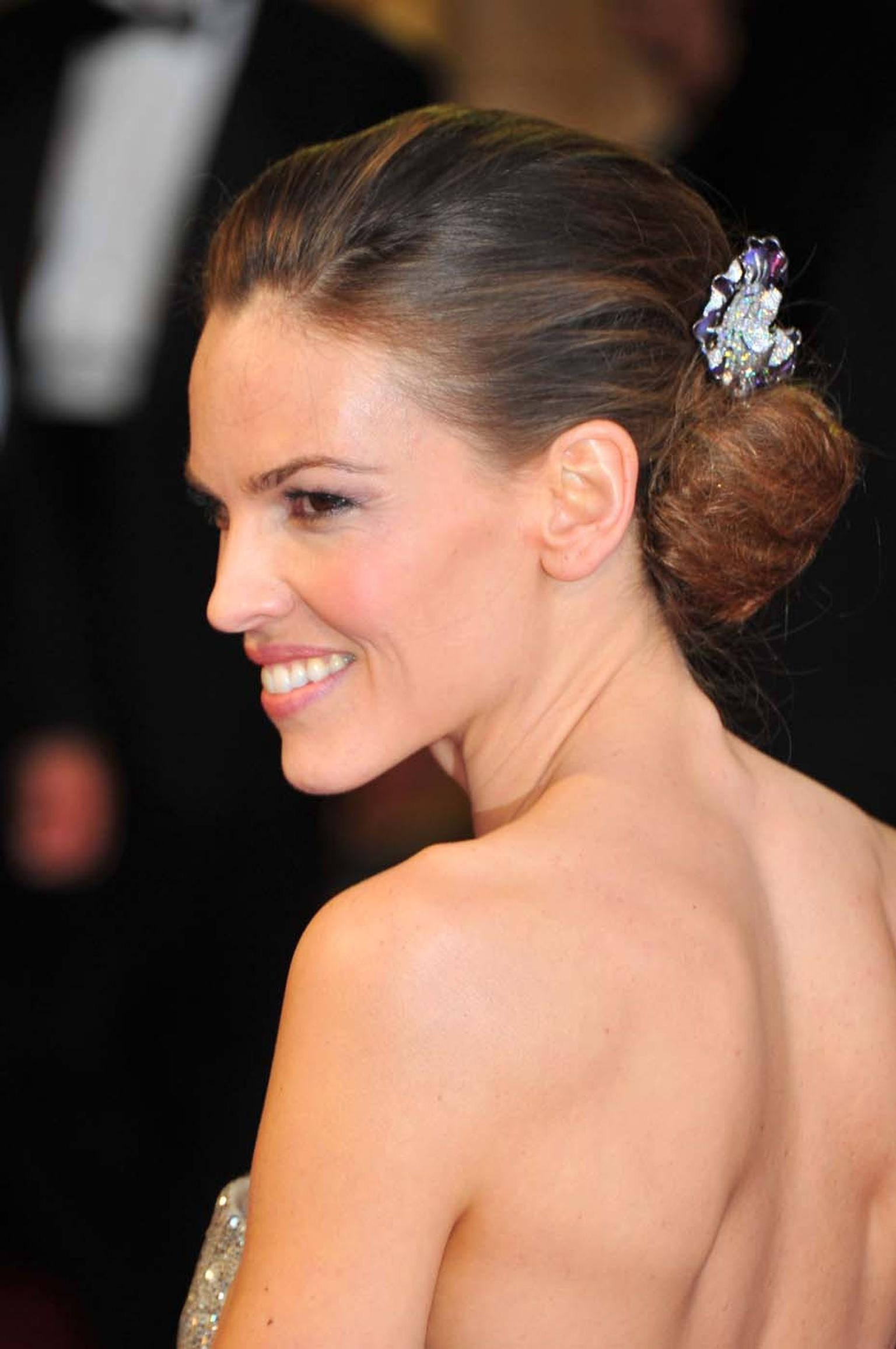 Hilary Swank wore a pair of Myth of Orchid high jewellery earrings by Anna Hu as hair ornaments to the 2011 Oscars.