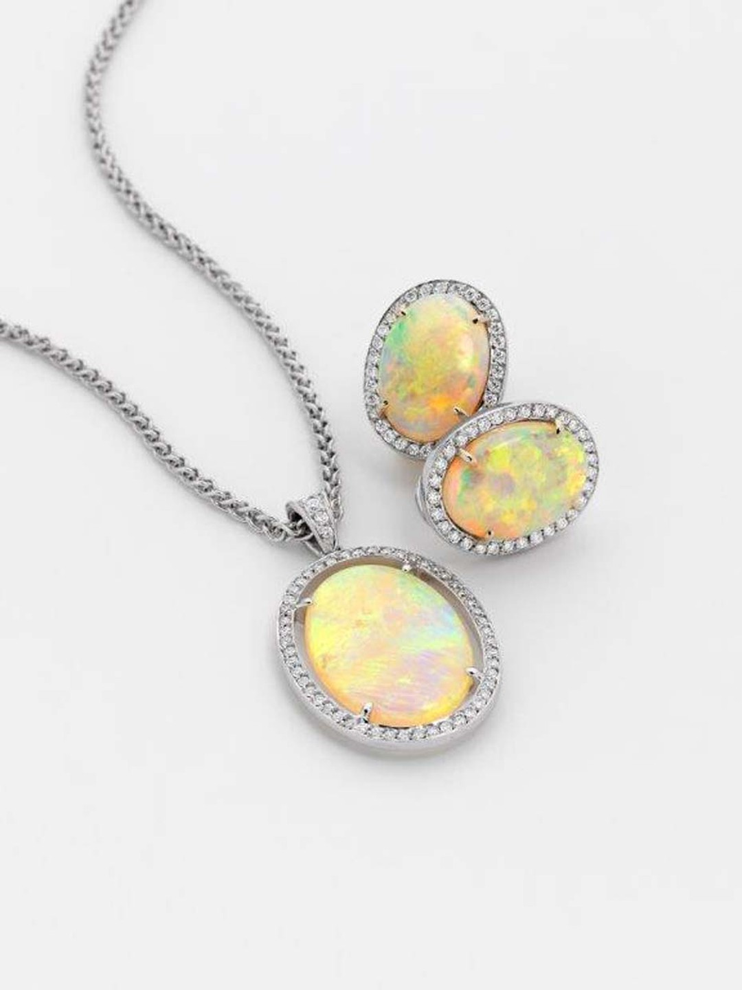 Percy Marks pendant featuring a 7.05ct Coober Pedy opal with brilliant-cut white diamonds on a white gold wheat chain, with matching earrings.