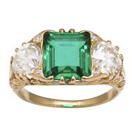 A La Vieille Russie Victorian engagement ring in gold with a central-set Colombian emerald flanked by old-mine diamonds.