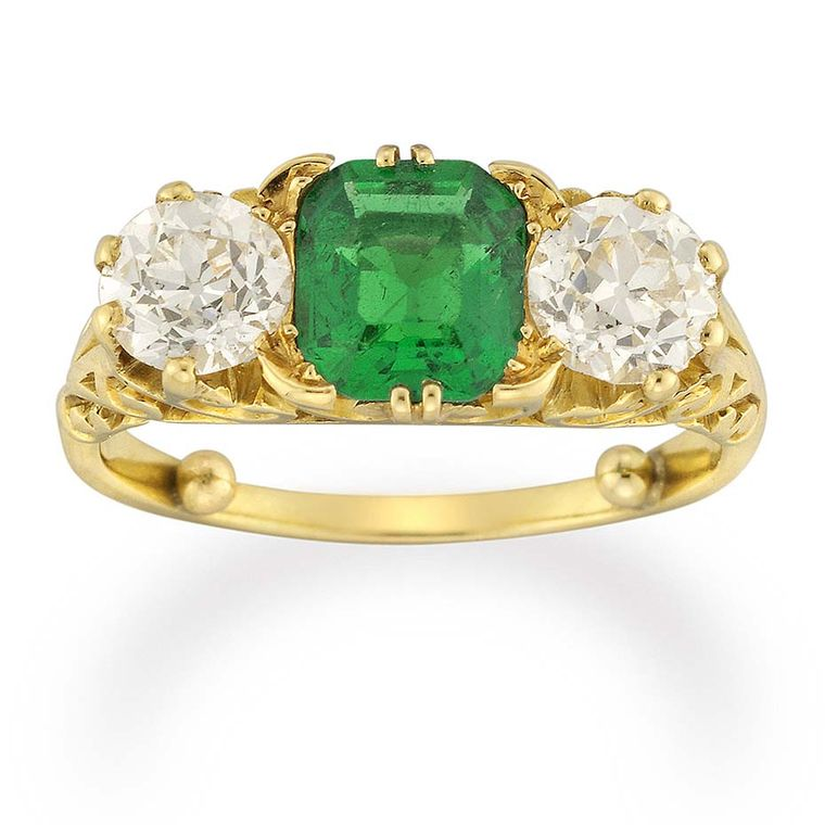 An emerald sits in the centre of this three stone Victorian engagement ring from Bentley & Skinner, flanked by two old-cut diamonds in a carved yellow gold mount.