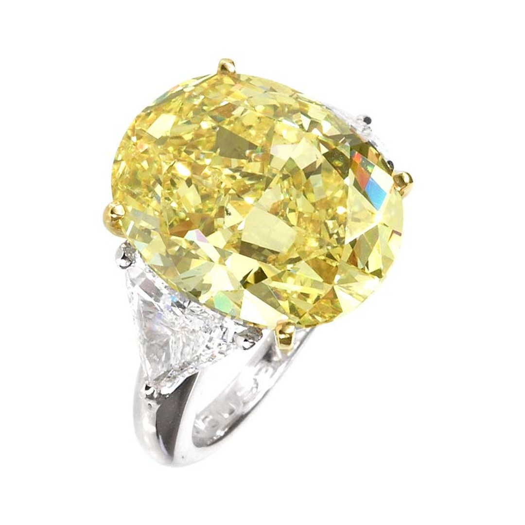 Moussaieff oval cut 14.23ct Natural Fancy Intense Yellow diamond flanked by 1.84ct trillion diamonds and mounted in platinum.