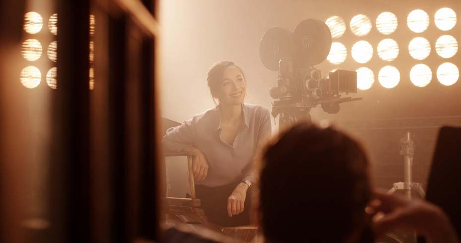 Carmen Chaplin is captivated by a silent movie, possibly starring her grandfather Charlie Chaplin, surrounded by film equipment of his era and lit by the hazy light of studio spotlights during the shoot for Jaeger-LeCoultre's new Open a Whole New World ad