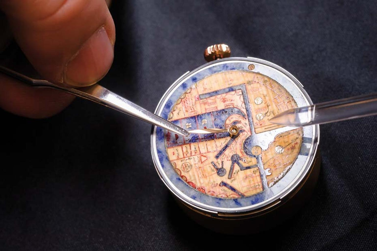 The blue sodalite stone on the dial of the Pearl of Wonders watch has been decorated with miniature inlaid pieces of papyrus to recreate the texture and colour of the original parchment.