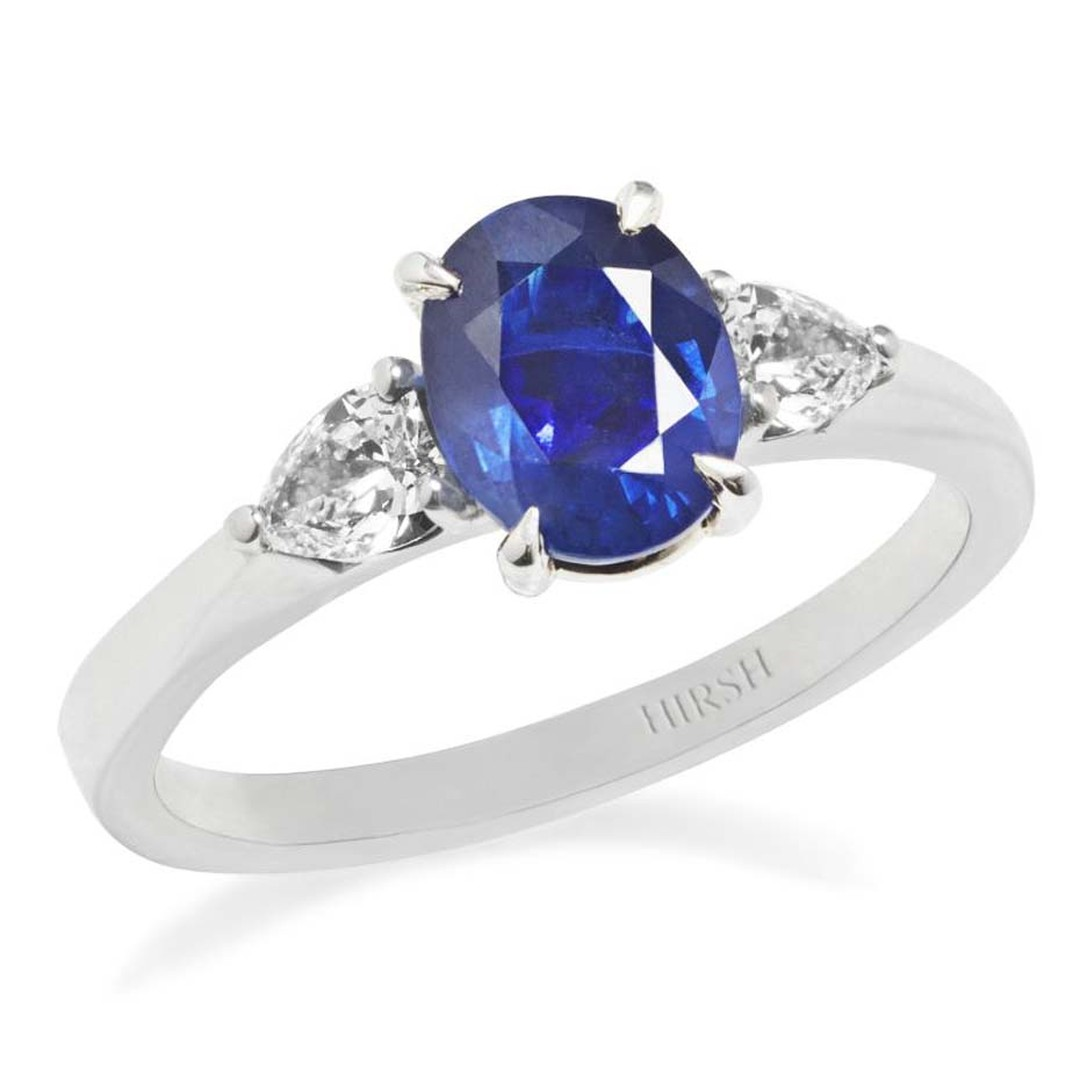 A blue sapphire ring with diamond side stones will never go out of fashion, like this Hirsh jewellery engagement ring with an oval-cut central sapphire, between two pear-shaped diamonds.