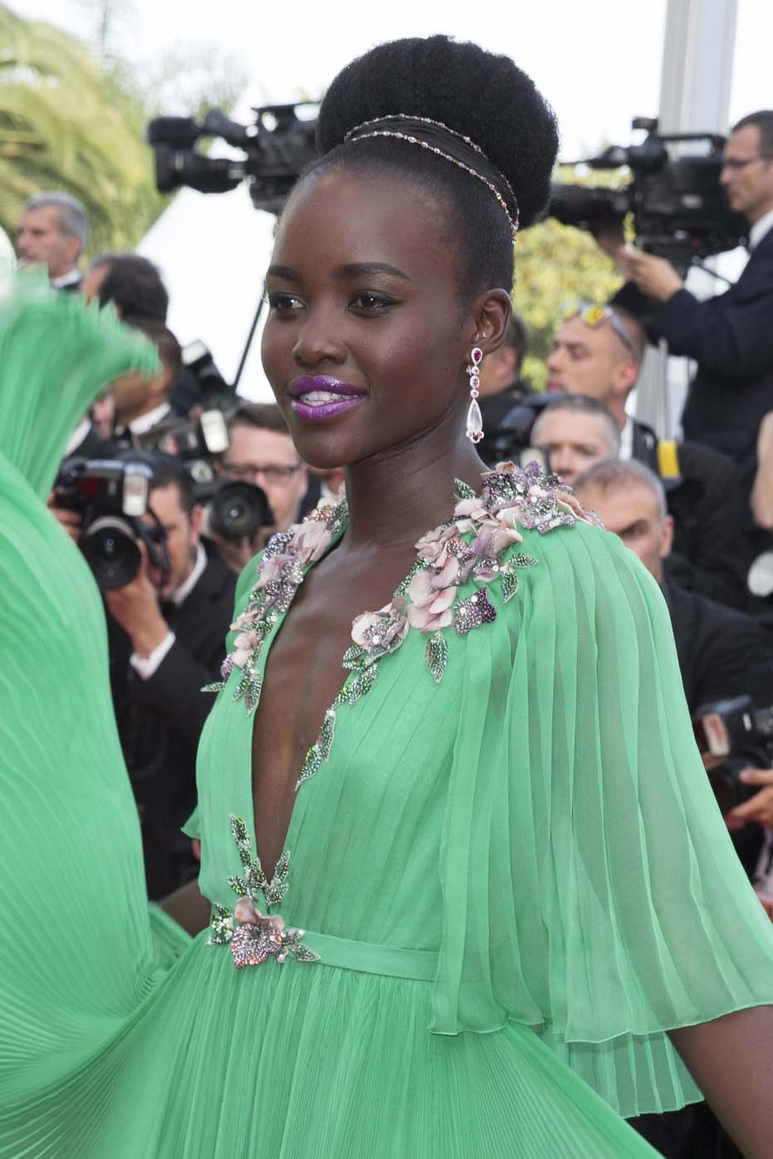 Oscar-winning actress Lupita Nyong'o stepped onto the red carpet of the 68th annual Cannes Film Festival wearing a swirling mint green Gucci gown, accessorised with a pair of Chopard Red Carpet collection diamond drop earrings.