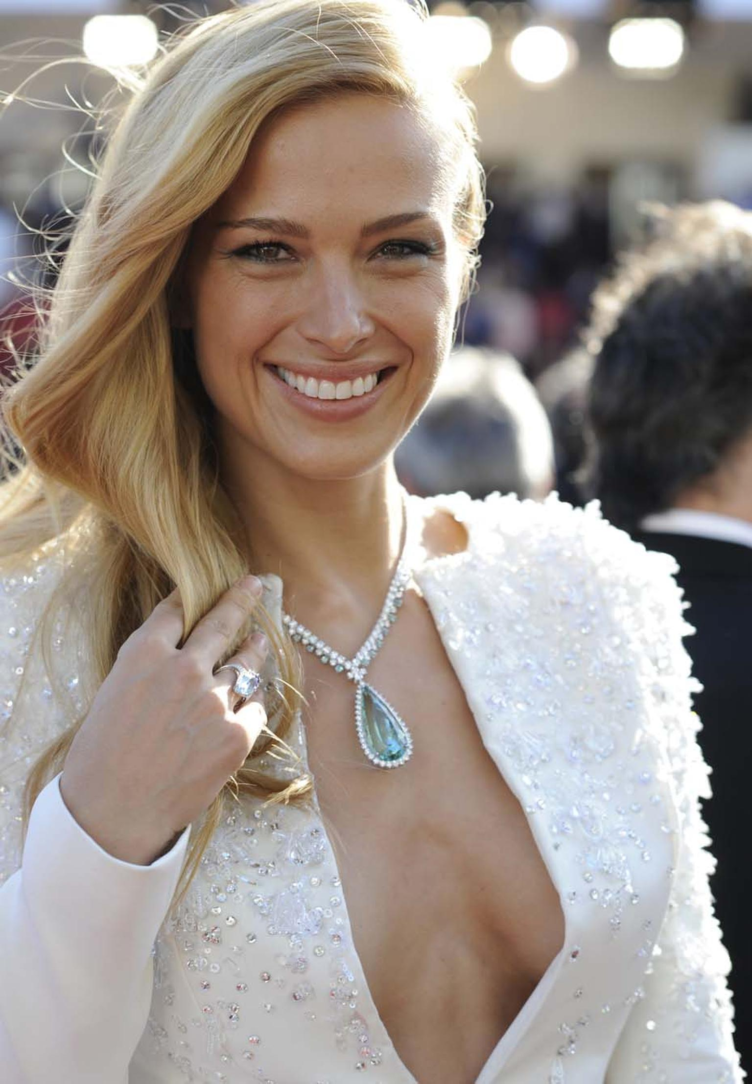 Chopard Ambassadress Petra Nemcova chose a green beryl and diamond high jewellery necklace from the Maison's Red Carpet collection, and a coloured gemstone ring from the Temptations collection, to contrast her all-white Zuhair Murad jacket and skirt combo
